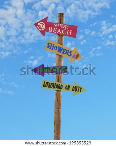 wooden four arrow direction signs post to the nude beach, showers, snacks and a lifeguard against a blue sky