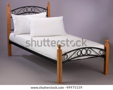 Wooden frame bed with white bed sheet.