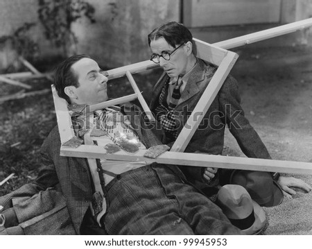 Wooden frame broken over two mens heads