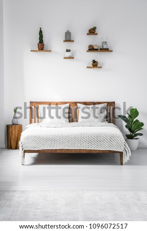 Wooden framed double bed with two pillows and a blanket, and small shelves above in a white bedroom interior. Real photo. #1096072517