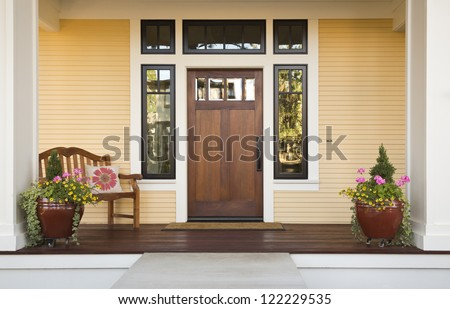 Wooden front door of a home. Front view of a wooden front door on a yellow house with reflections in the window and a wide view of the porch and front walkway. Horizontal shot.