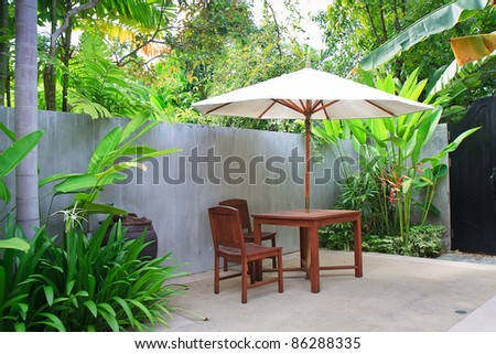 Wooden furniture covered by umbrella in garden , Thailand. #86288335