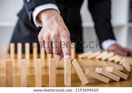 Wooden game strategy, Businessman hand stopping falling wooden dominoes effect from continuous toppled or risk, strategy and successful intervention concept for business.