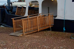wooden gangway with railing mounted on the pier for boarding the ship