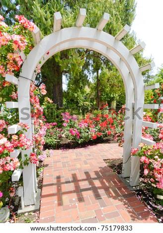 wooden garden arch in a pink flower garden