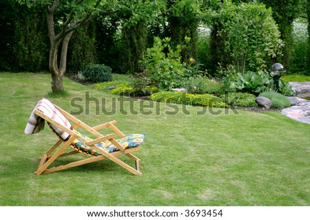 wooden garden chair in beautiful green garden