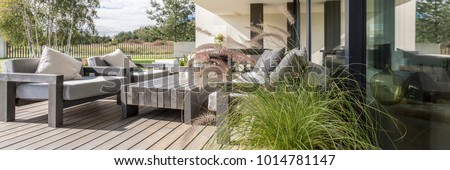 Wooden garden furniture on terrace with a floor constructed of wood boards