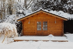 Wooden garden shed covered with snow. First snow. Winter in the garden