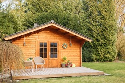 Wooden garden shed with terrace. Wooden garden shed. Life in the country in Germany in summer. Vacation in the country.