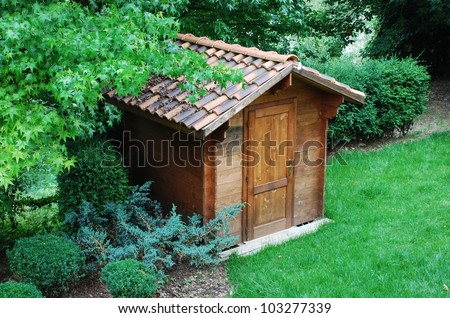 Wooden garden tool shed in a beautiful park - stock photo
