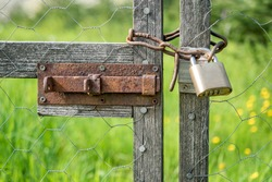 Wooden gate chain link fence locked with padlock, shallow depth of field, focus on padlock