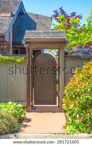 Wooden gate, wicket to the house entrance with nicely trimmed and landscaped front yard.