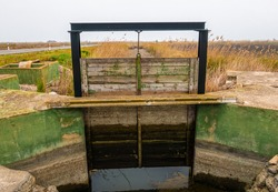 Wooden gates in an irrigation ditch, to measure the entry and exit of the water flow from the rice fields.