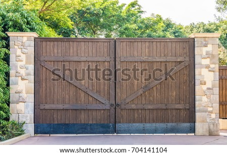 Wooden gates with stone columns. The design is vintage style.