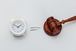Wooden gavel and alarm clock