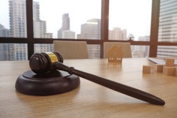 Wooden gavel and block set on the table with house model for property and real estate auction. Lawyer and judgement for prosecution case of land and property and filing a lawsuit concept.