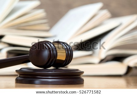 wooden gavel and books on wooden table #526771582