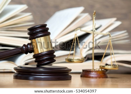 wooden gavel and books on wooden table #534054397