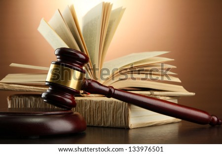 wooden gavel and books on wooden table,on brown background