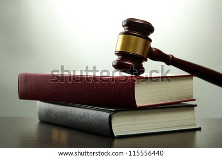 wooden gavel and books on wooden table,on grey background