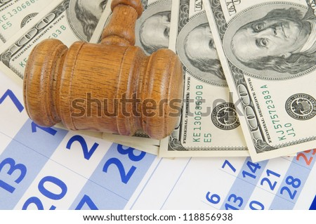 Wooden gavel and money on paper calendar