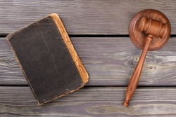Wooden gavel and old law book. Court and justice concept. Grey desk background.