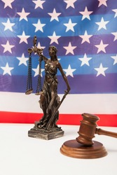 wooden gavel and statuette of justice near american flag on background