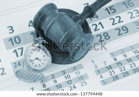 Wooden gavel and watch on paper calendar