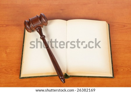 Wooden gavel from the court and opened law book on wooden background. Shallow DOF