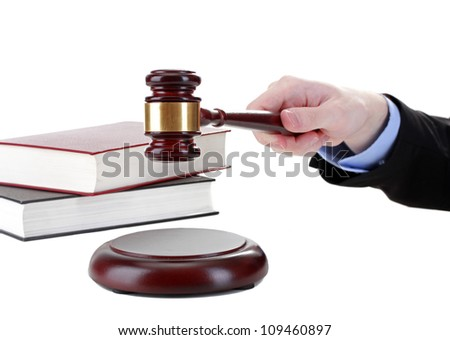 wooden gavel in hand and books isolated on white