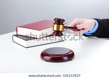 wooden gavel in hand and books on gray background