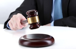 wooden gavel in hand on gray background