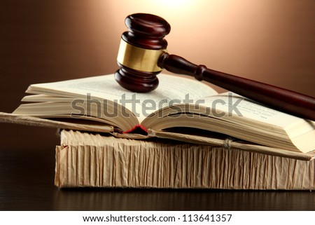 wooden gavel on books, on brown background