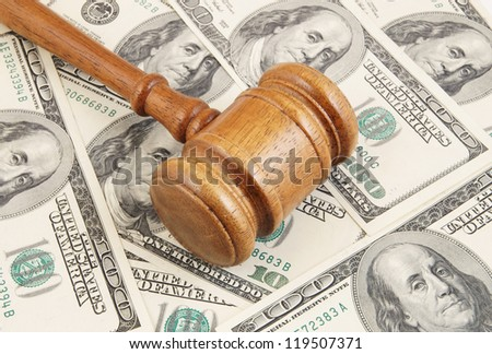 Wooden gavel on dollars background