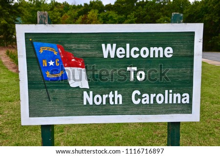 Wooden green colored with white letters Welcome signpost to North Carolina