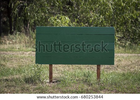 Wooden green plate on the posts for inscription. In the park, Surface for inscription, background #680253844