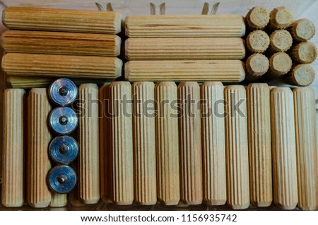 Wooden grooved dowels organized in different patterns n a clear container, with four steel dwel pins