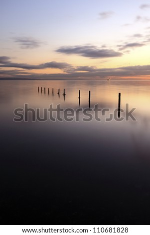 Wooden groynes leading in to the sea at Sunset, from Saltcoats on the west coast of Scotland
