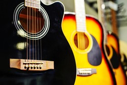 Wooden guitars of different shapes and colors. Trade in acoustic instruments in a shop. Close-up