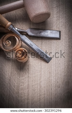 Wooden hammer curled up planning chips flat chisels on wood board construction concept.