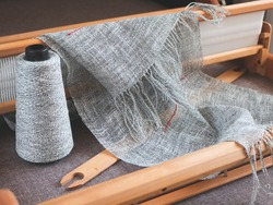 Wooden handloom, reed, shuttle, bobbin with linen yarn and piece of woven cloth. Handwoven fabric made of natural linen fiber