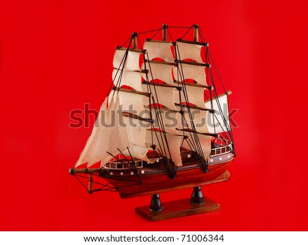 Wooden handmade clipper ship for home decoration on red background