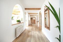Wooden handmade mirror in hallway boho interior. Home indoors design concept.