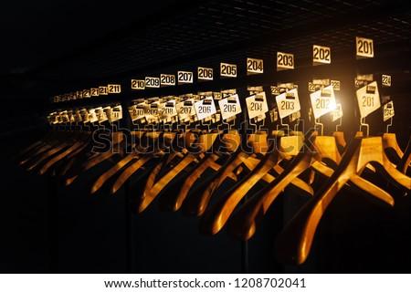 Wooden hangers with numbers in dark cloakroom.