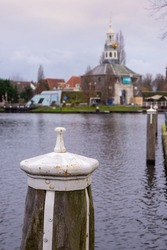 Wooden harbor peer with white metal protection with the blurry buildings in the background