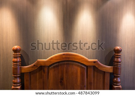 Wooden headboard in a dark bedroom lit by down lights on the ceiling #487843099