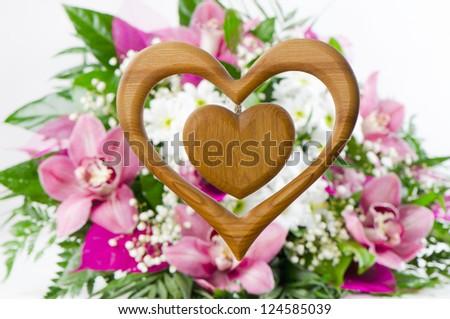 Wooden heart on flower background