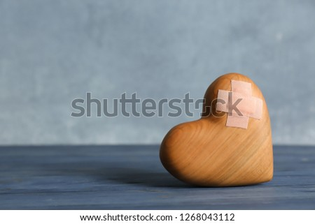 Wooden heart with adhesive plasters on table. Space for text