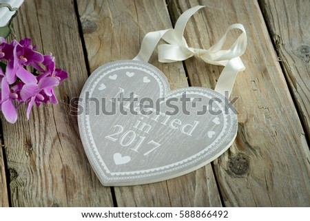 wooden heart with logo married in hands holding table sign grey #588866492