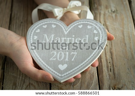 wooden heart with logo married in hands holding table sign grey #588866501